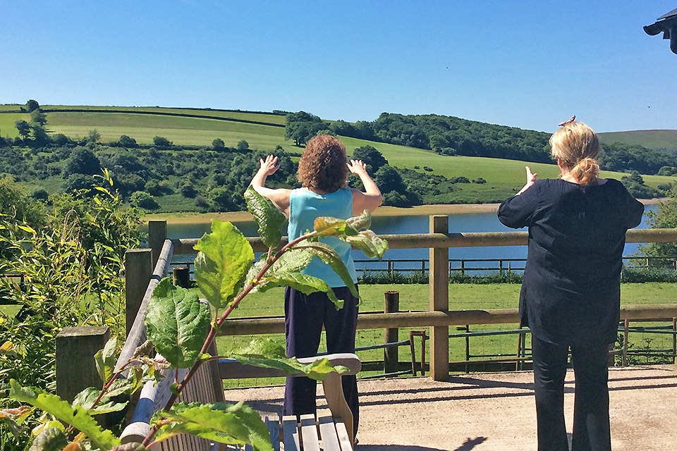 Two women performing gentle movements by Wimbleball Lake
