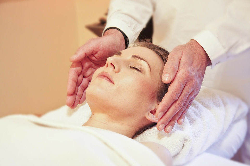 Woman relaxing while receiving Craniosacral Therapy
