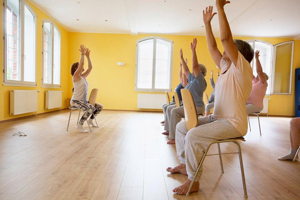 Instructor running chair yoga class